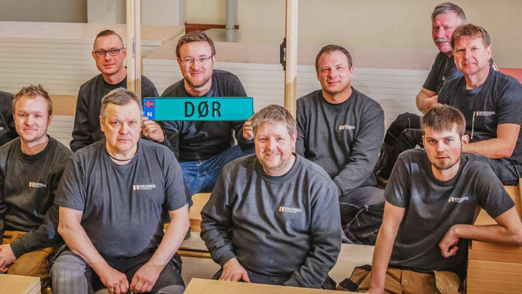 NEKTES: Roar Knudsen (med skiltet) og Knudsen Dørfabrikk får ikke bruke bilskiltet de betalte 9000 kroner for. Her er bedriftseieren med deler av staben. Foto: Knudsen Dørfabrikk
