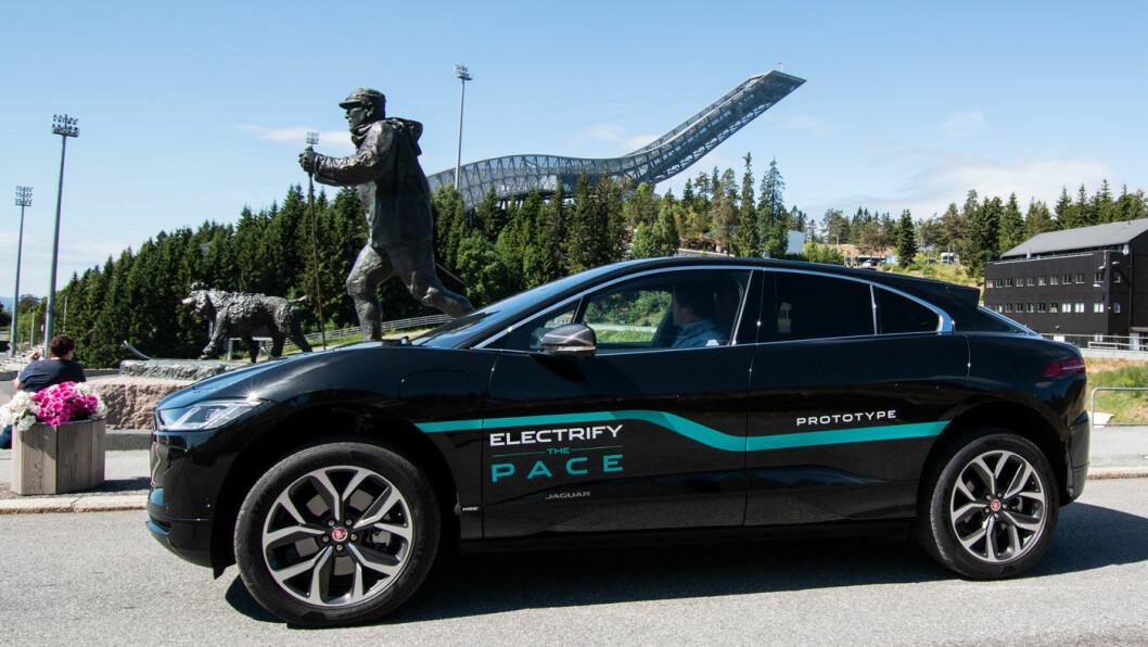 KONGEMØTE: Jaguar I-Pace kan med stor selvtillit stille seg opp ved siden av folkekongen Olav. Rent fysisk kan kanskje I-Pace kjøre unnarennet i Holmenkollen opp, mer billedlig er det også sjansen for at den hopper bakken ned i konkurranse med de andre elbilene. Foto: Peter Raaum