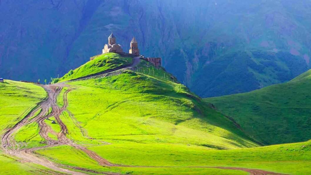 ET LANDEMERKE: Gergeti treenighetskirke ligger på 2170 meter over havet. Om været tillater det får vi et glimt av den snødekte toppen på Kazbek-fjellet, et av Kaukasus høyeste fjell.