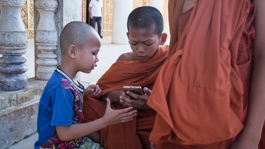 SJEKKER MOBILEN: Som så mange andre steder, er mobilen midtpunkt også for disse små guttene ved den imponerende Vipassana Dhura-pagoden i Oudong, Kambodsja.