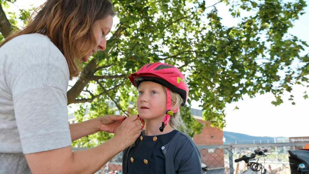 TRYGG MED HJELM: Marie er klar for å sykle til skolen med ny hjelm. Mamma Janne Pedersen, seniorrådgiver i NAFs forbrukeravdeling, minner om at en god hjelm minsker risikoen for hodeskader dramatisk. Foto: Anette Berve / NAF