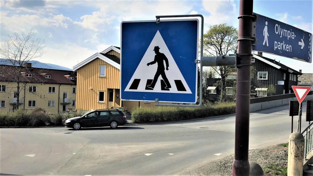 GÅR OG GÅR: Her er mannen med hatt fotografert i Lillehammer sentrum. Legg merke til at her møtes gammel og ny tid på samme skiltstolpe. Robot-figuren til høyre viser vei til Olympiaparken. Foto: Geir Røed