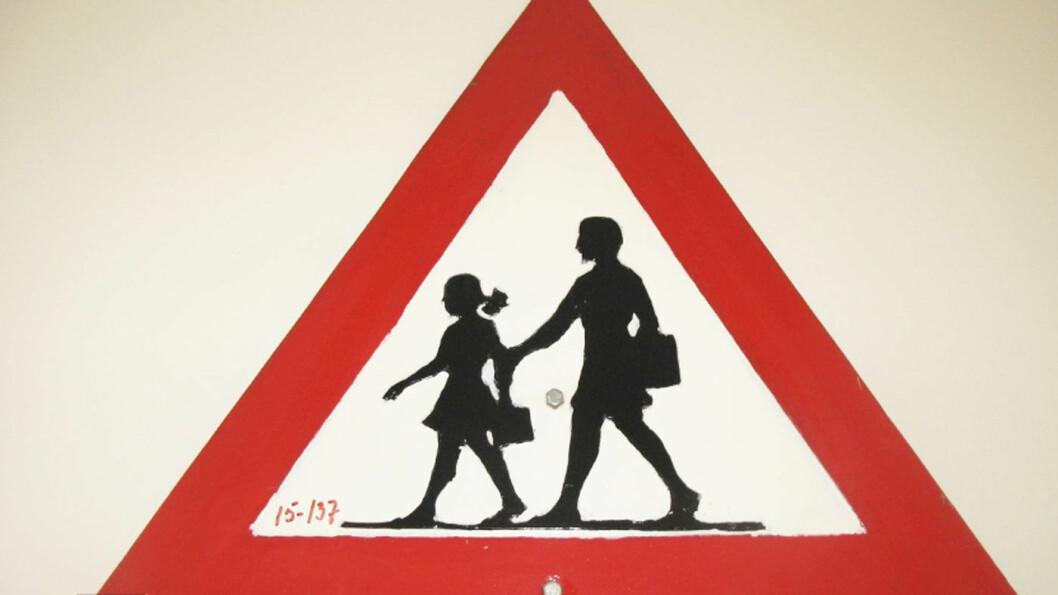 MUSEFLETTER: Fareskiltet som viser barn slik det var, og noen steder fortsatt er, med jente med musefletter og skjørt, og en gutt, begge med ransler. Foto: Vegmuseet