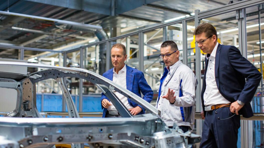 EN LITEN SJEKK: Volkswagens toppsjef Herbert Diess (t.v.) får en innføring i ID.3-produksjonen ved VWs nye elbilfabrikk i Zwickau av to av sine medarbeidere. Foto: Volkswagen AG
