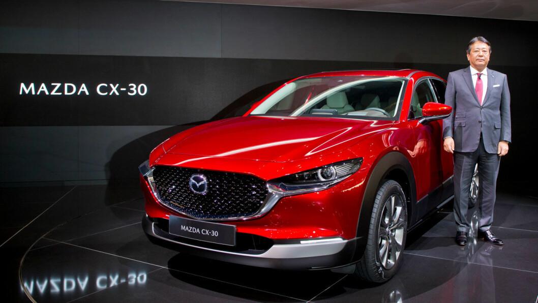DESIGNBOMBE: Mazda lager lekre biler, og den kommende elbilen blir neppe noe unntak. Her er Mazda-sjef Akira Marumoto ved siden av nye CX-30-modellen under årets bilutstilling i Genève. Foto: Mazda