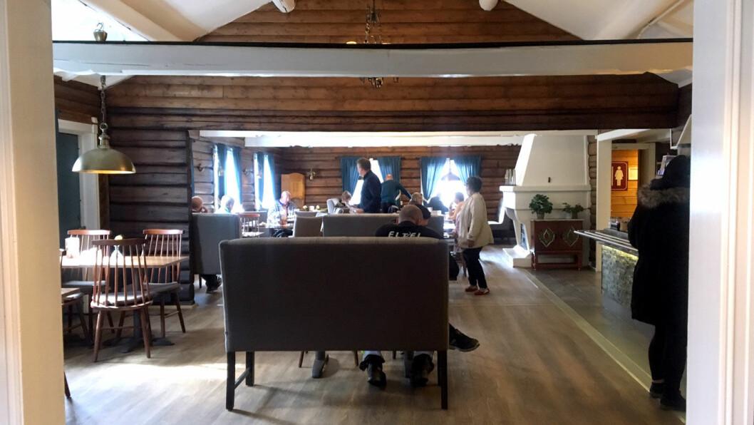 ET TRIVELIG STED: Mørke tømmervegger, gode sofaer og stoler, peis og en flott skiferdisk med smørbrød og kaker gjør dette til en hyggelig og populær veikro.