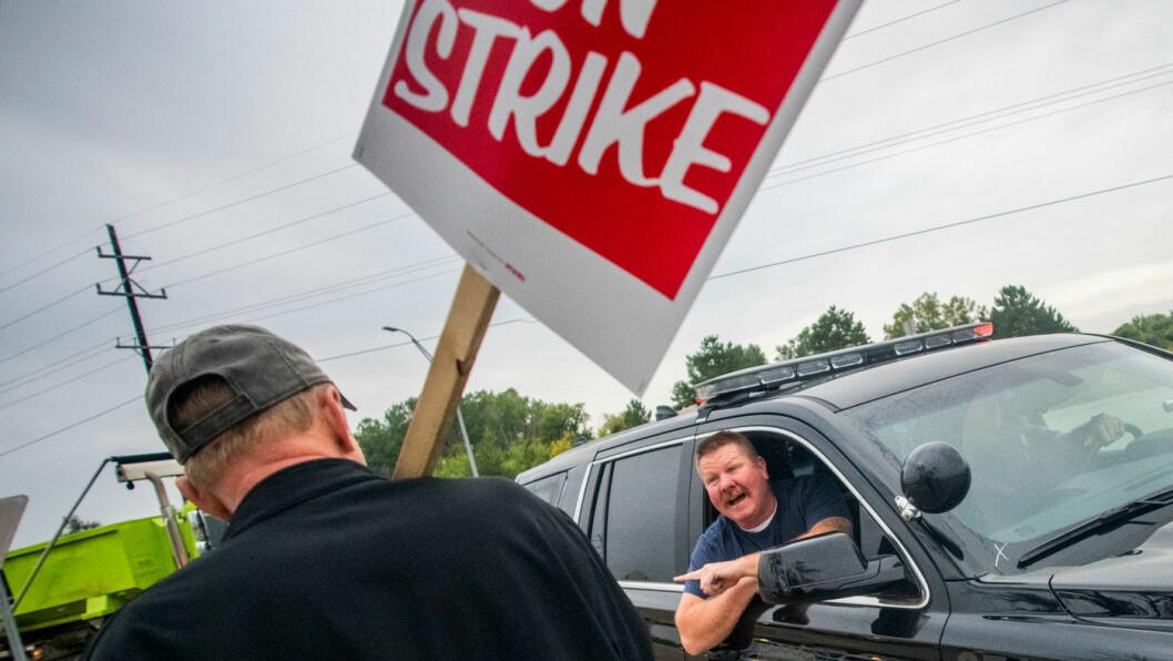 STORSTREIK Nærmere 50.000 arbeidere hos den amerikanske bilgiganten General Motors gikk mandag ut i streik. Her ber politiet i Flint, Mićhigan en streikende om at trafikken får slippe forbi. Foto: AP / NTB scanpix