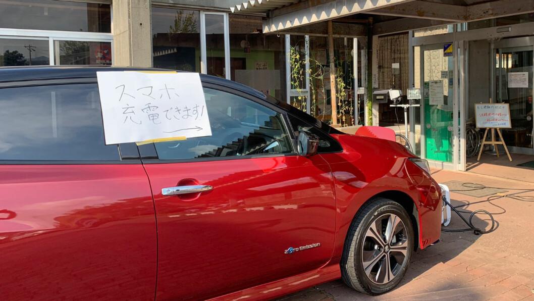 STRØMBANK: En Nissan Leaf oppstilt utenfor et kommunalt kontor i Chiba-prefekturet, med påskrevet beskjed om at man kan lade sine mobiltelefoner her. Foto: Nissan