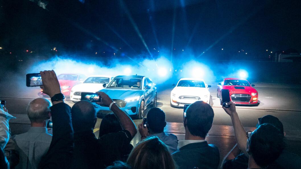 SLUPPET LØS: Fords første elbil, Mustang Mach-e, ble lansert i Los Angeles i natt. Her med en blå GT-utgave i midten blant et knippe Mustang-legender. Foto: Peter Raaum