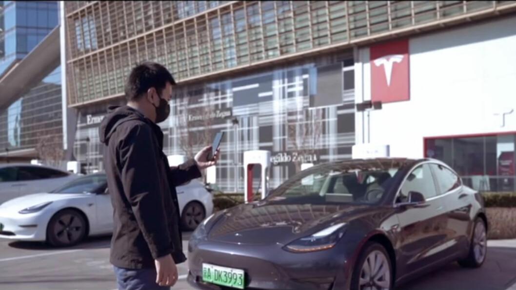 SALG VIA MOBIL: Den potensielle kunden får instruksjoner fra en selger via smarttelefonen for å hente en bil for prøvekjøring. Foto: Skjermdump fra reklamefilm for Tesla på Bilibili