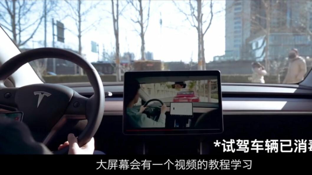 VIRUSBESKYTTET: Kunden får veiledning fra selger under prøvekjøringen, men all fysisk kontakt unngås. (Skjermdump fra reklamefilm for Tesla på Bilibili).