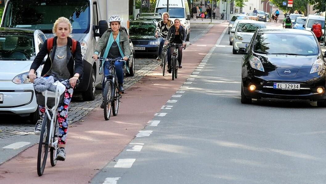 RØD LØPER: Røde sykkelfelt i Bispegata i Trondheim er ett av mange tiltak i byen for å skille syklistene fra gående og bilister. Foto: Knut Opeide