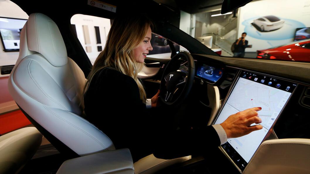 SJELDEN KOST: Bare 6 prosent av Tesla-kjøperne er kvinner. Her er en spansk kvinne som utforsker displayet på en ny Tesla under åpningen av den første Tesla-butikken i Spania, i L'Hospitalet de Llobregat nord for Barcelona, i september. Foto: EPA/Alejandro Garcia