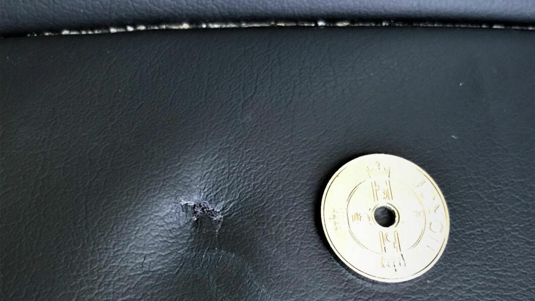 DYRT HULL: Det lille hullet i setetrekket er ikke stort større enn hullet inne i kronestykket. Reparasjon hos Motor Forum koster 21 000 kroner. Foto: Brian Lein