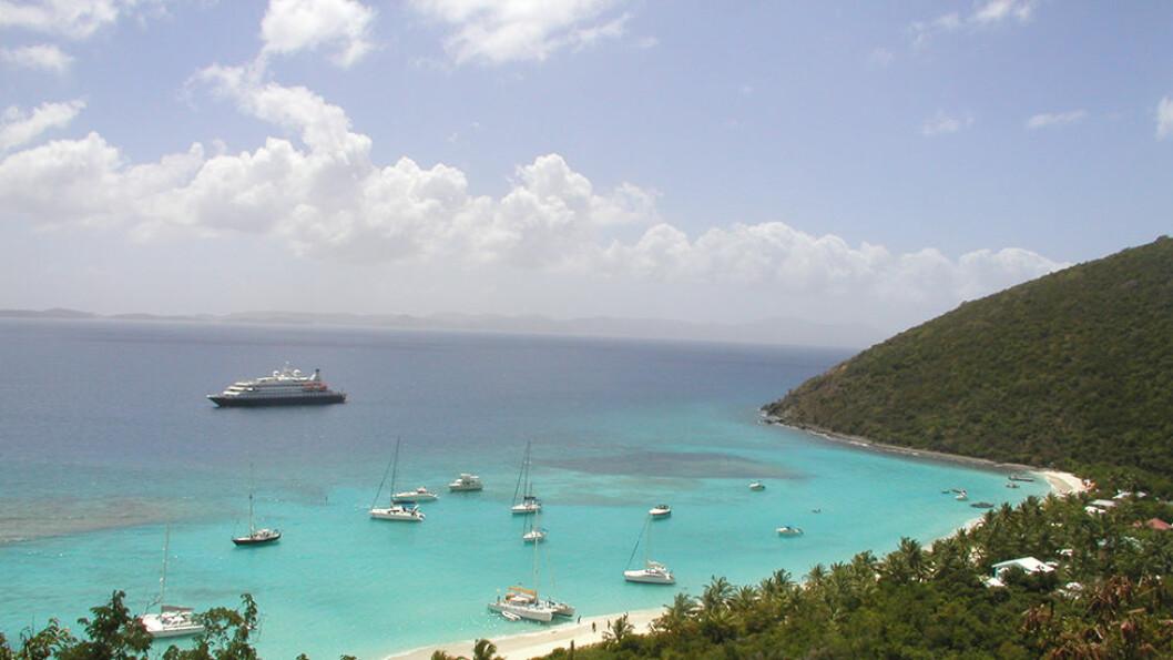 En av SeaDreams små luksusyachter ligger for anker utenfor en strand i Karibien