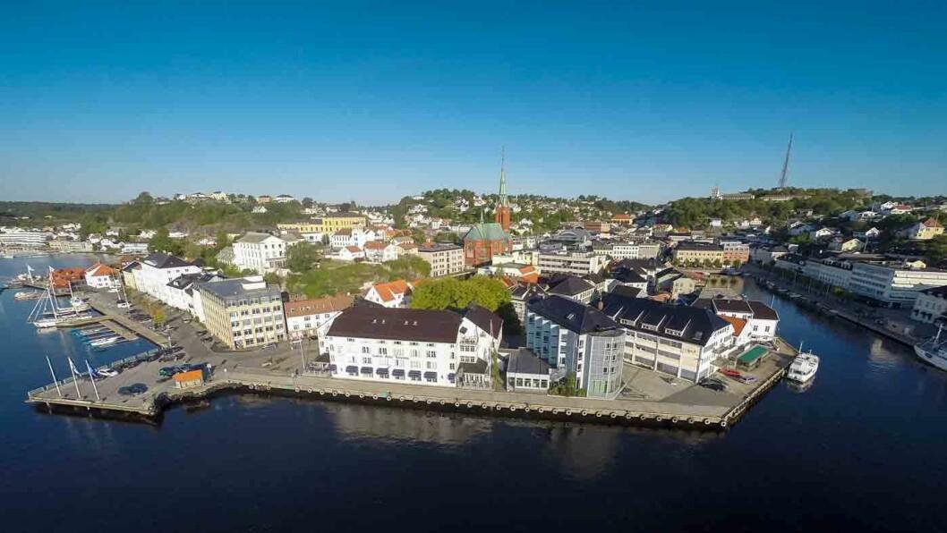 ARENDALS STORSTUE: Hotellet i det lave, hvite bygget glir godt inn i den hvite trebebyggelsen på Tyholmen.