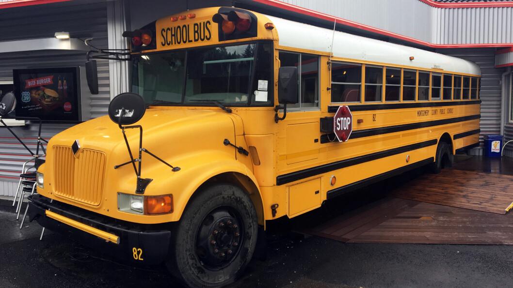 TA PLASS: Den gule, amerikanske skolebussen er kjørt inn i veggen og gir flere sitteplasser i kafeen.