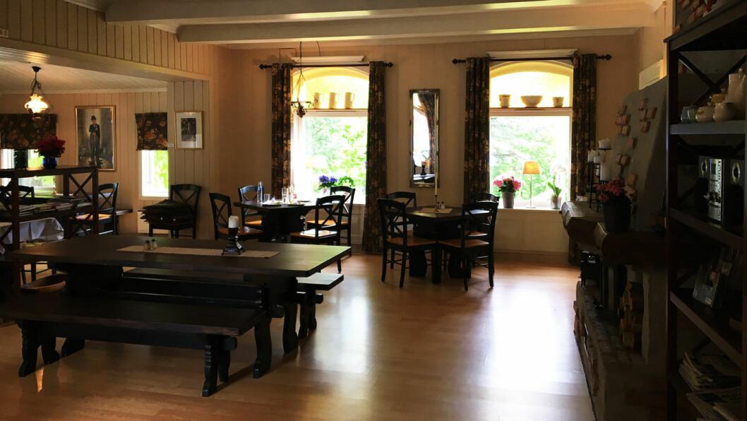 ENGELSK STIL: Veldig hyggelig interiør med store vinduer, friske blomster og lys på bordene.