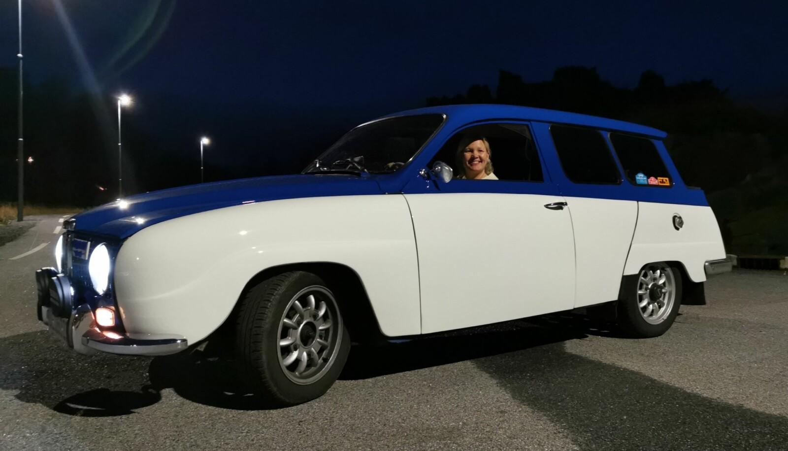 <b>EN AV TRE SAAB-ER: </b>Nina Jensen Kristiansen gjør Bergen blidere med sin helt spesielle hvit- og blålakkerte Saab stasjonsvogn. Familiehunden Sason er oppkalt etter etternavnet til Saabs berømte designer, Sixten Sason og dukket ned da bildet ble tatt.