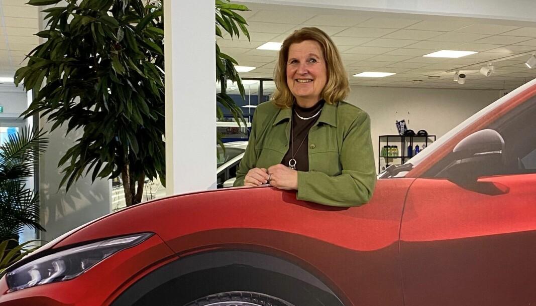 """<span class=""""font-weight-bold"""" data-lab-font_weight_desktop=""""font-weight-bold"""">PAPIRBIL:</span> Wenche Kristiansen Johre godtar Motors småtøysete idé om å fotografere henne med Ford-forhandlerens papp-utgave av Mustang Mach-E, mens hun venter på den ordentlige bilen hun har bestilt. I det minste er fargen, Rapid Red, den samme."""