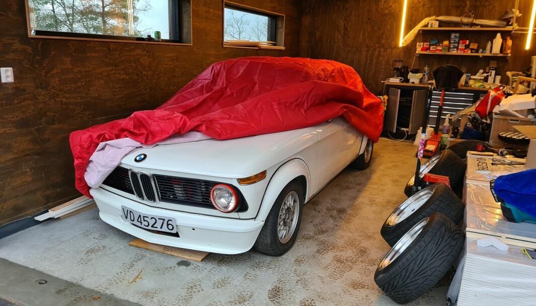 """<span class=""""font-weight-bold"""" data-lab-font_weight_desktop=""""font-weight-bold"""">NISSELUE:</span> Christian Røren kommer i julestemning med rød lue på «nissen på låven», eller garasjen. Hans BMW 2002 får godt stell hele året, også gjennom høytiden."""