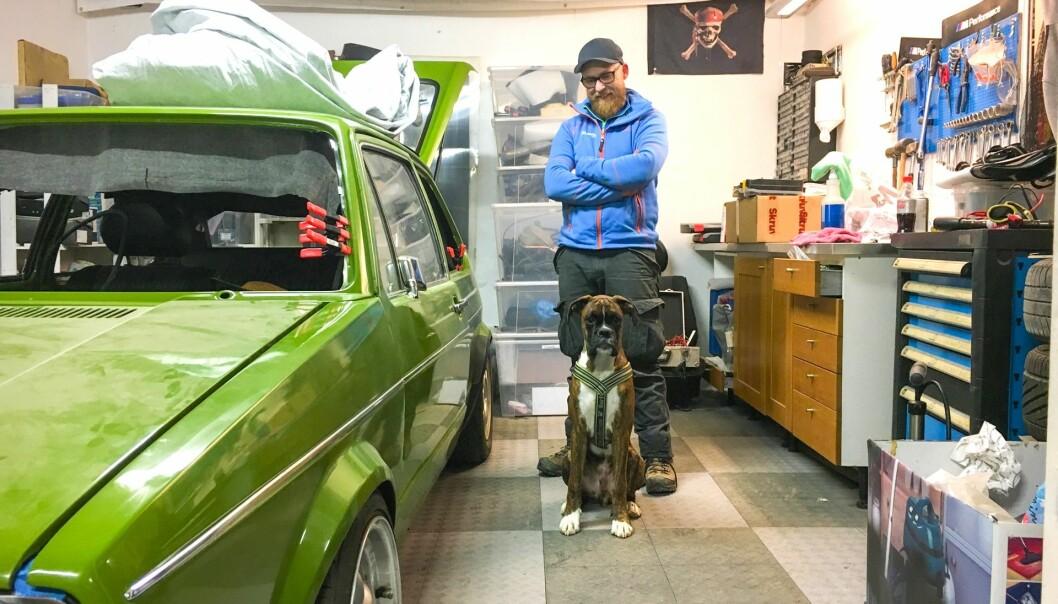 """<span class=""""font-weight-bold"""" data-lab-font_weight_desktop=""""font-weight-bold"""">FAMILEMEDLEM: </span>Joachim Næss, hans grønne Golf og boxeren Knirk på en improvisert garasjeplass i en låve forut for familiens flytting. Hunden er dessverre i mellomtiden gått bort."""