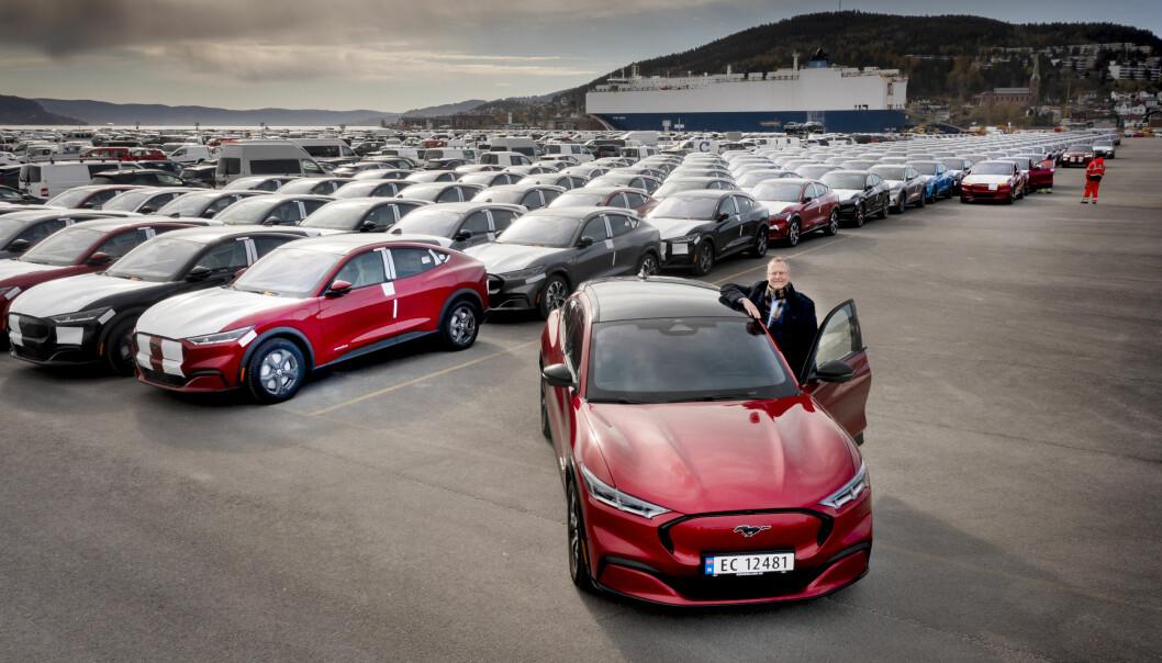 FØRSTE BÅTLAST: Nå strømmer det Ford Mustang Mach-e inn i landet via Drammen havn. Ford-sjefen i Norge står her foran et knippe av de først ankomne.