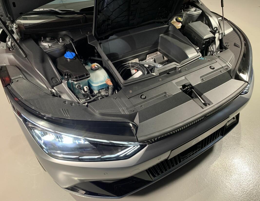 """<span class="""" font-weight-bold"""" data-lab-font_weight_desktop=""""font-weight-bold"""">FRUNK: </span>Det praktiske oppbevaringsrommet under panseret er utformet som en eske med lokk. Her oppbebares adaptere til 230-volts uttak som gjør at man kan bruke strøm fra bilens batteri til elektriske apparater, eventuelt lade en annen elbil."""