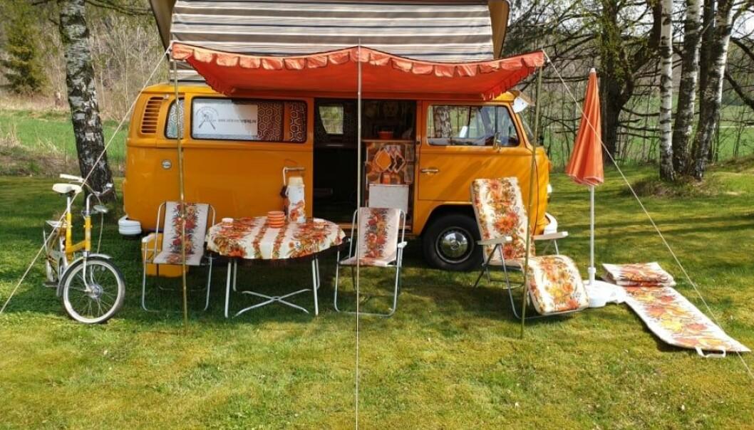 """<span class=""""font-weight-bold"""" data-lab-font_weight_desktop=""""font-weight-bold"""">ORANGUTANG: </span>Roar Kristiansens Folkevognbuss fra 1978 har Devon DoubleTop hevetak og innredning fra Bobil-interiør a/s i Oslo – også bygd i 1978. Sykkelen er en DBS Kombi Butterfly fra 1972 – og parasoll, campingstoler og campingbord stammer fra samme tiår."""