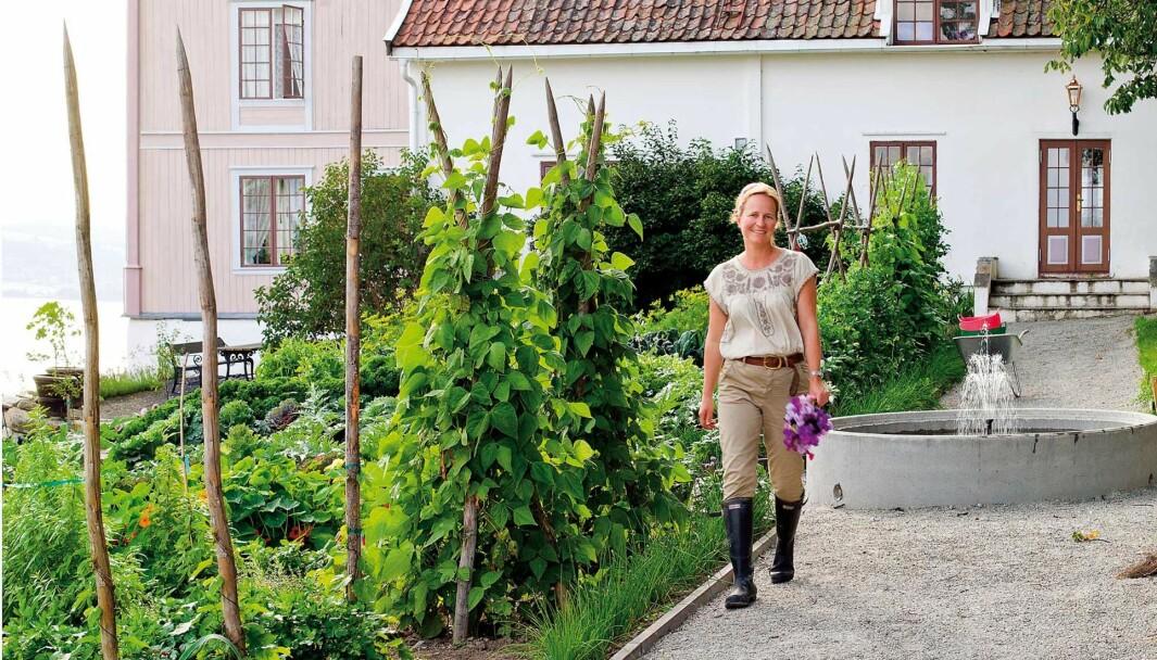 TIL GARDS: Marianne Olssøn ønsker gjester velkommen til besøkshagen og gårdsbutikken på Helgøya, fire mil fra Hamar.